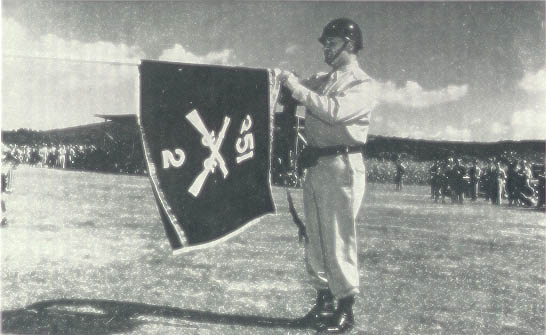 Lieutenant General John Lee, Commanding General of US Army Forces in the Mediterranean Theater, fastens the Distinguished Unit Citation Streamer to the colors of the 2nd Battalion 351st Infantry Regiment.